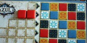 Spieler 2 legt die beiden roten Fliesen passend auf sein Tableau.