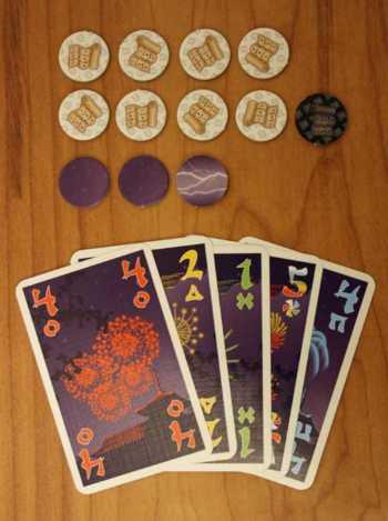 """Spielvorbereitungen: Der """"Meister"""" legt die Hinweis- und Gewitter-Plättchen aus, die Spieler erhalten die ersten Feuerwerkskarten."""