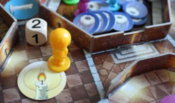 Der gelbe Spieler würfelt eine zwei und zieht über die Treppe zwei Räume weiter.