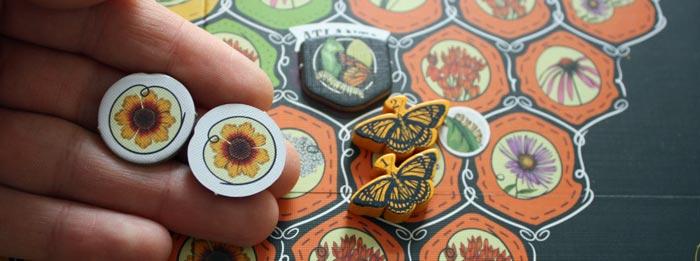 """Beipiel 2: Der Spieler landet neben einer Seidenpflanze. Er """"zahlt"""" 2 Blüten und erhält einen Schmetterling."""
