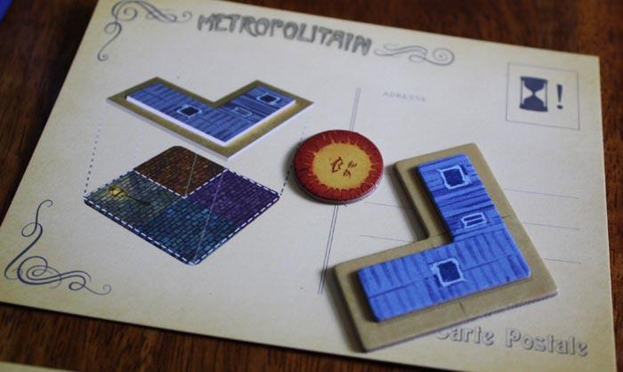 Der Spieler entscheidet sich für die Postkarte Metropolitain und erhält ein zusätzliches Gebäude.